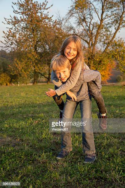 Portrait of boy giving his sister a piggy back ride on a meadow