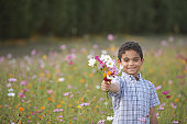 Portrait of boy holding bouquet of flowers in field