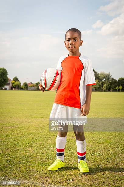 Portrait of boy holding football on pitch