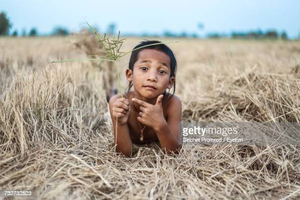 Portrait Of Boy Holding Grass Gesturing While Lying On Field Against Sky At Farm