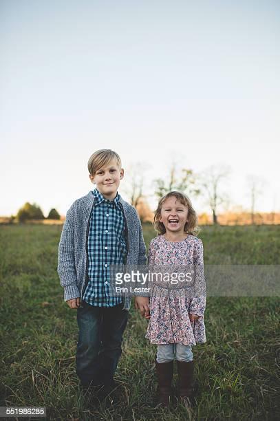 Portrait of boy holding sisters hand in field