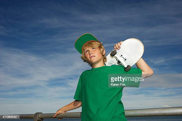 Portrait of boy holding skateboard over shoulder