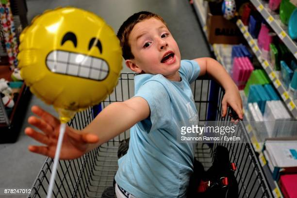 Portrait Of Boy Holding Toy While Sitting In Shopping Cart