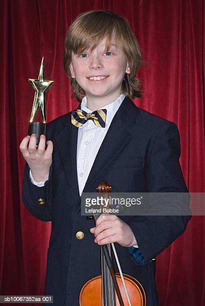 Portrait of boy (10-11) holding violin and trophy