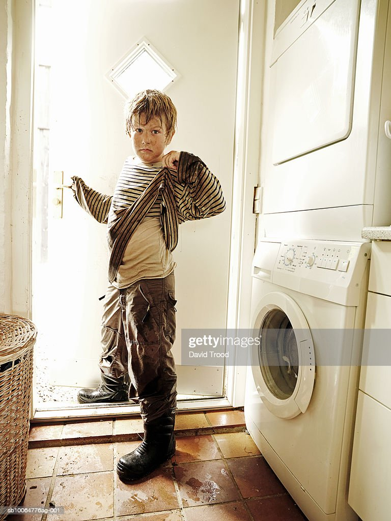 Portrait of boy (8-9) in dirty clothes standing in front of washing machine