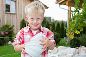 Portrait of boy in garden carrying stack of bowls