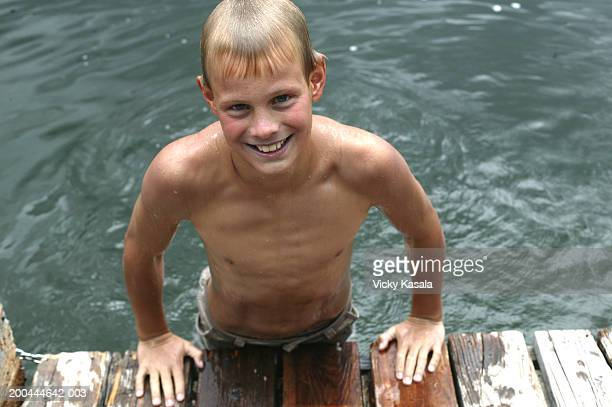 Portrait of boy (11-13) leaning on edge of pier, smiling