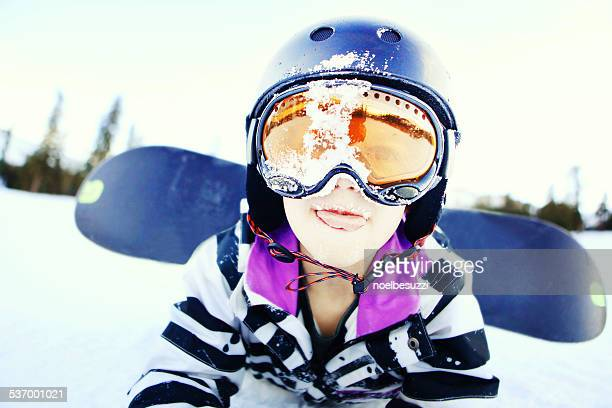 Portrait of boy lying in the snow with a snowboard