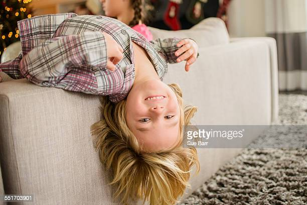 Portrait of boy lying upside down over sofa at christmas