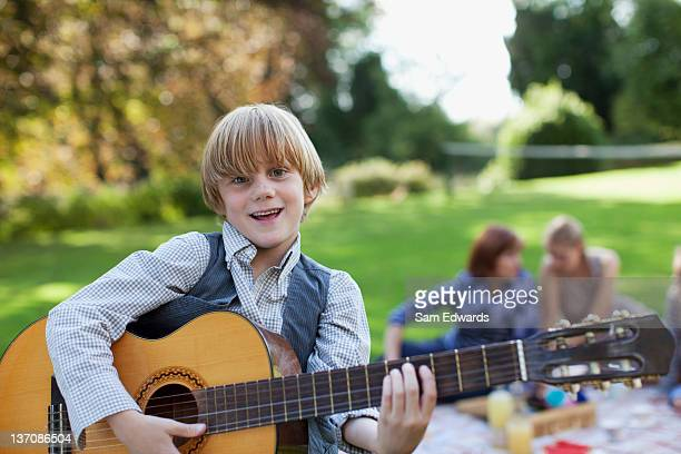 Portrait of boy playing guitar in park