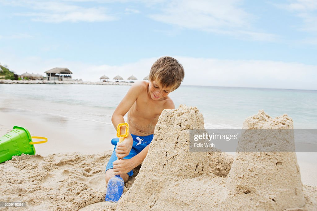 Portrait of boy (10-12) playing on beach in sand building castle : Foto de stock