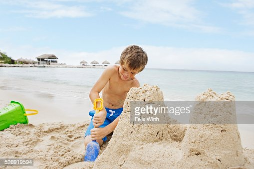 Portrait of boy (10-12) playing on beach in sand building castle : Stock Photo