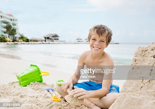 Portrait of boy (10-12) playing on beach in sand : Stockfoto