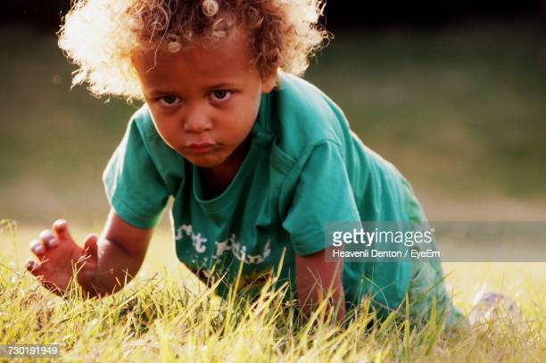 Portrait Of Boy Playing On Grassy Field