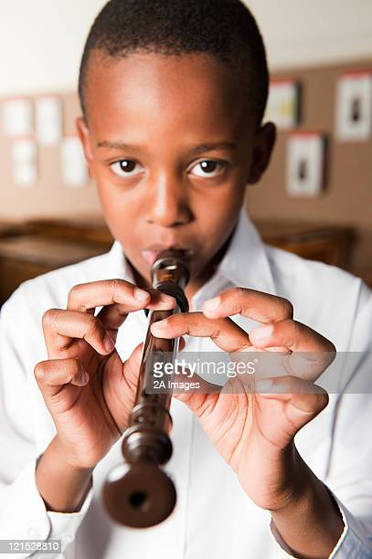 Portrait of boy playing recorder in classroom, Johannesburg, Gauteng Province, South Africa