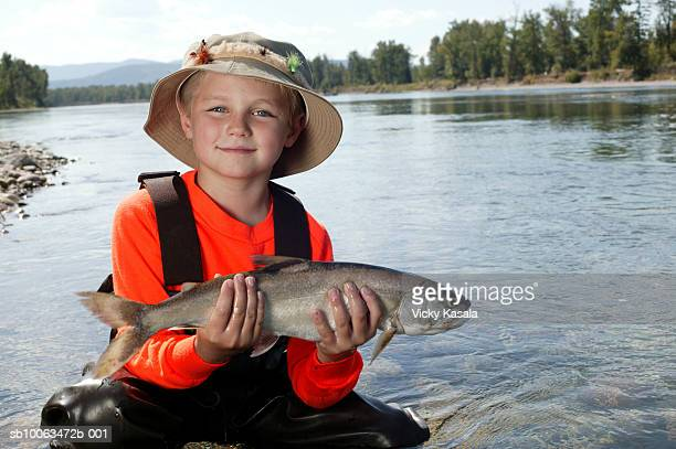 Portrait of boy (6-7) posing with fish by river, smiling