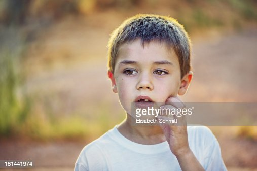 Portrait of boy, scratching his cheeks