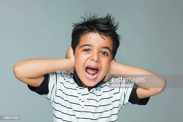 Portrait of boy (6-7) shouting and covering ears with hands