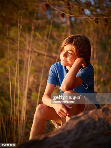 Portrait of boy sitting gazing from rock, Majorca, Spain