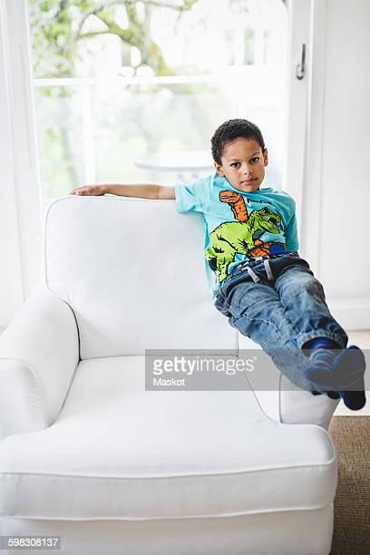 Portrait of boy sitting on handrest of armchair at home