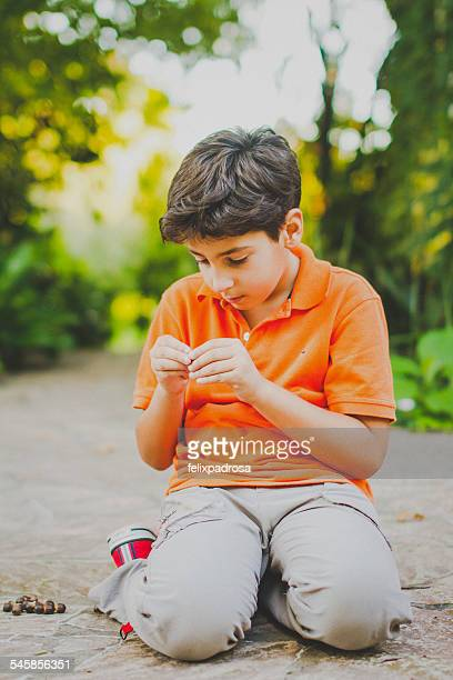Portrait of boy (10-11) sitting on park alley, looking at plant seeds