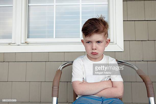 Portrait of boy sitting outside house sulking