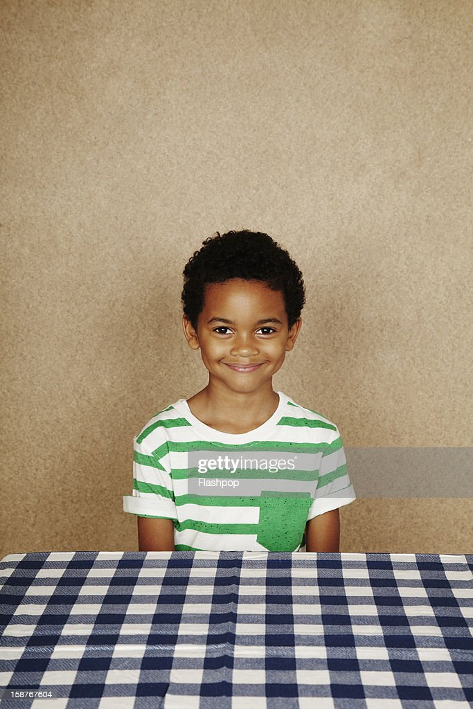 Portrait of boy smiling at dining table : Stock Photo