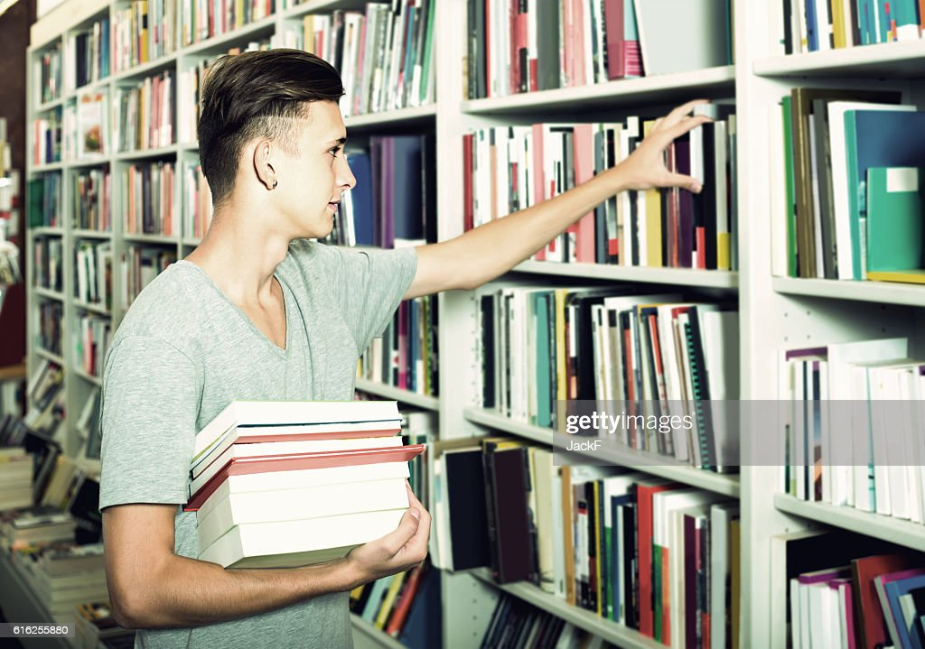 portrait of  boy standing among bookshelves and searching for bo : Foto de stock