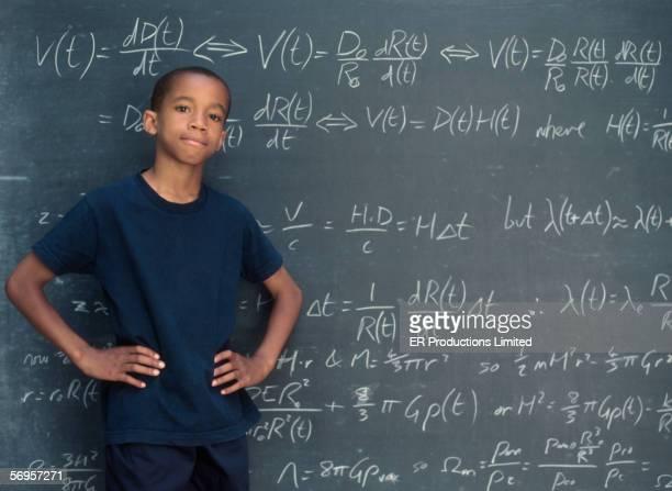 Portrait of boy standing in front of chalkboard