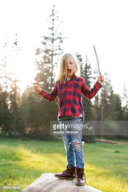 Portrait of boy (6-7) standing on rock in forest