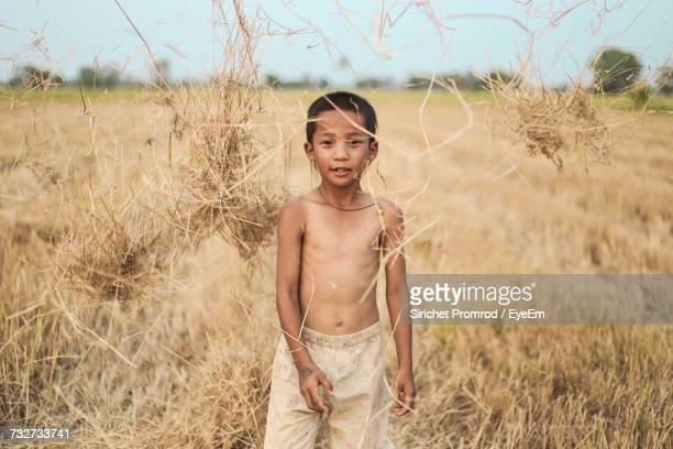 Portrait Of Boy Throwing Straws While Standing On Field At Farm Against Sky
