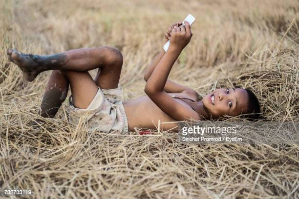 Portrait Of Boy Using Mobile Phone While Lying On Field At Farm