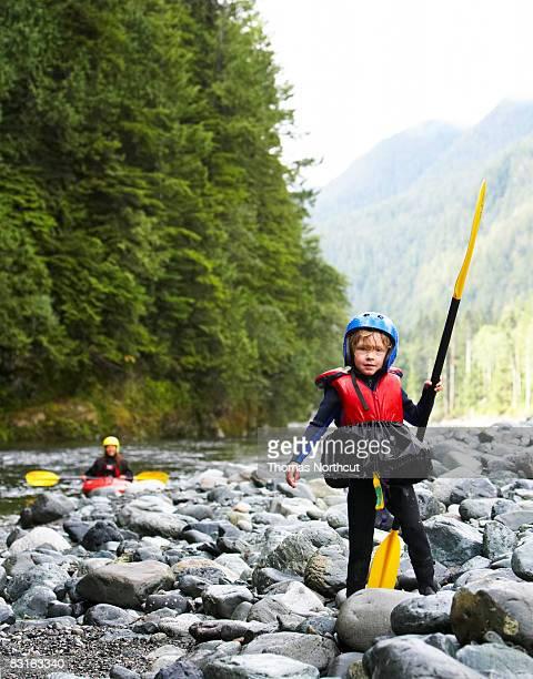 Portrait of boy wearing kayak gear holding paddle.