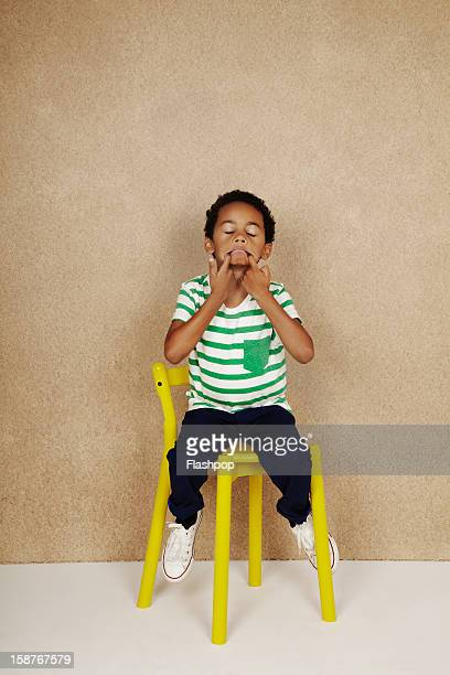 Portrait of boy with chair pulling funny faces