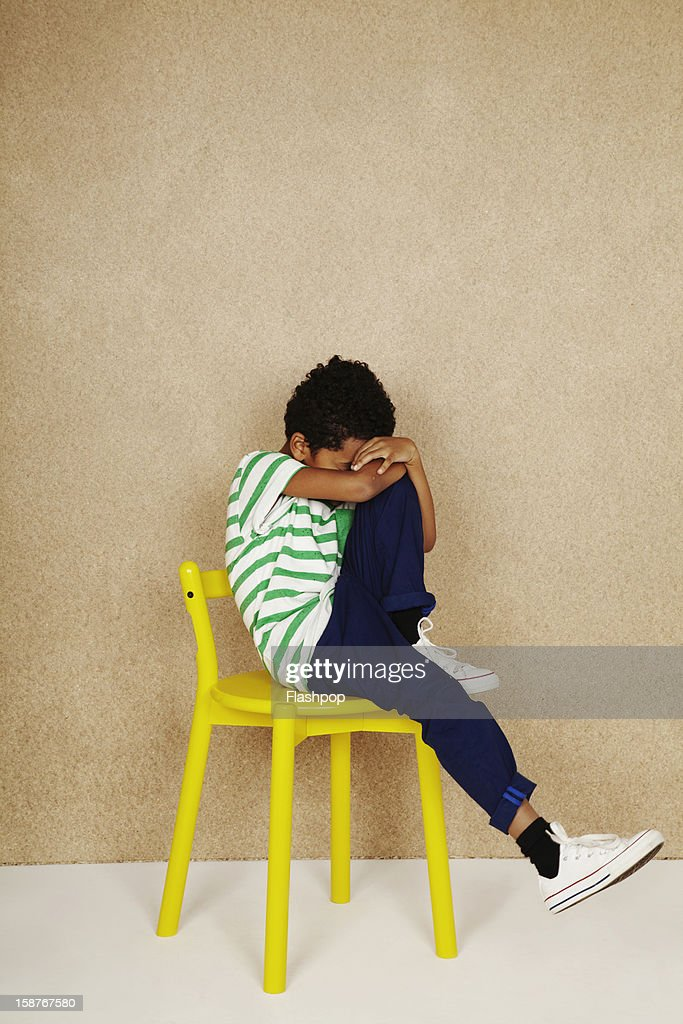 Portrait of boy with chair pulling funny faces : Stock Photo