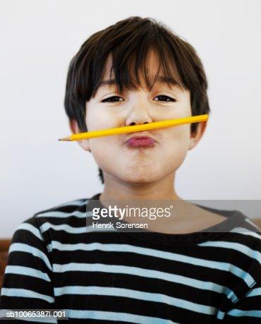 Portrait of boy (8-9) with pencil under nose : Bildbanksbilder