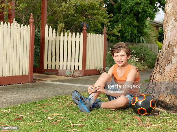 Portrait of boy with soccer ball sitting on grass tying trainer laces