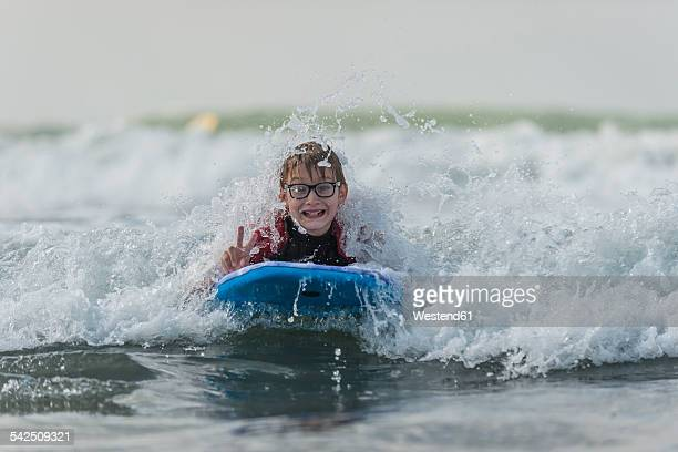 Portrait of boy with surfboard showing victory sign