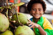 Portrait of boy wrapped in Brazilian flag selecting coconut on Ipanema beach, Rio De Janeiro, Brazil