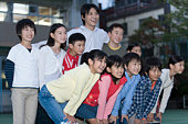 Portrait of boys and girls with male teacher smiling