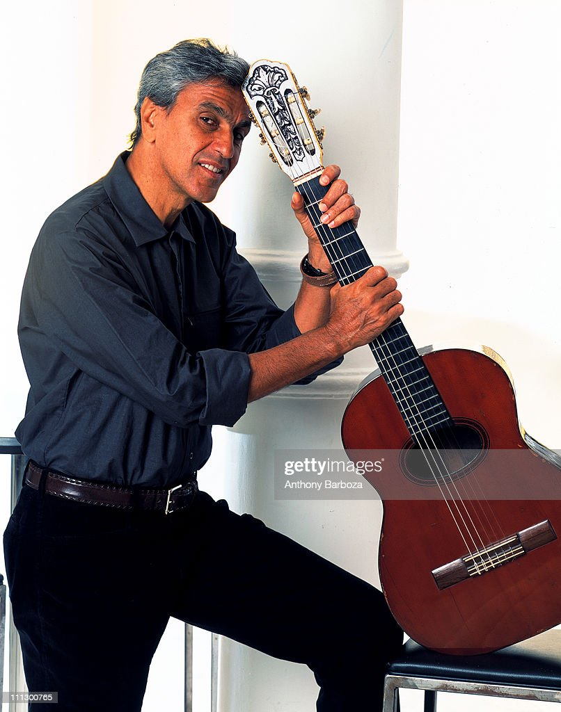 Portrait of Brazilian composer and musician Caetano Veloso, leaning on an acoustic guitar, New York, 2001.