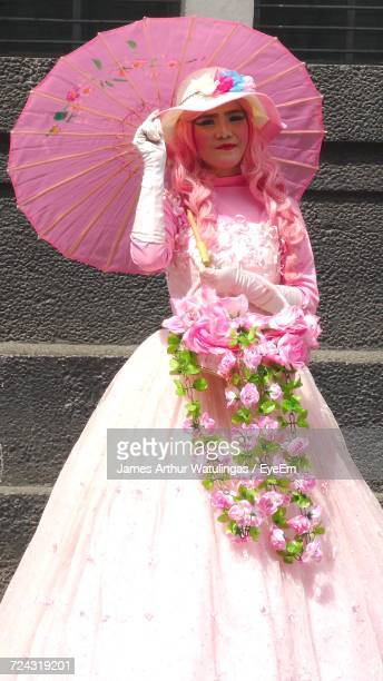 Portrait Of Bride Standing With Umbrella Against Wall