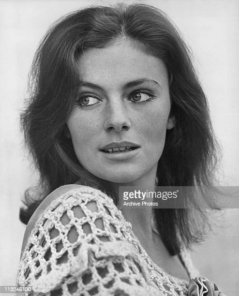 Portrait of British actress Jacqueline Bisset wearing a crocheted top and looking over her shoulder in the 1960's