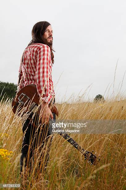 Portrait of British blues guitarist Marcus Bonfanti photographed with his Gibson SG electric guitar in a field in rural Norfolk on July 30 2013
