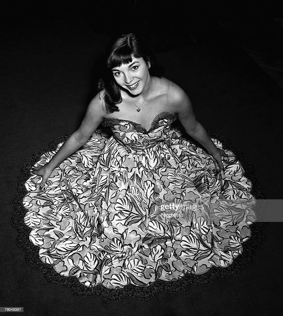 Portrait of British 'Film Starlet' Joan Collins seated on the floor and wearing a strapless printed evening dress (high angle looking down), 1951