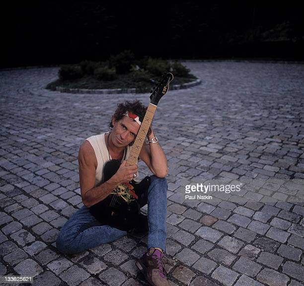 Portrait of British musician Keith Richards as he holds a guitar and sits on a settpaved driveway around the time of his 'Talk is Cheap' tour late...