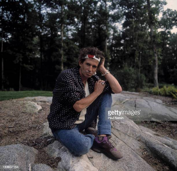 Portrait of British musician Keith Richards as he sits on a large rock around the time of his 'Talk is Cheap' tour late 1988