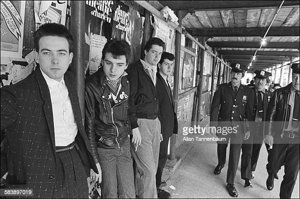 Portrait of British Rock group the Cure from left Robert Smith Simon Gallup Matthieu Hartley and Lol Tolhurst as they lean against a wall on Columbus...