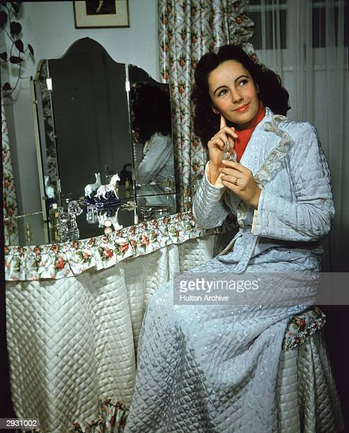 Portrait of Britishborn actor Elizabeth Taylor as she sits at a mirrortopped vanity table and applies perfume behind her right ear circa 1940s She...