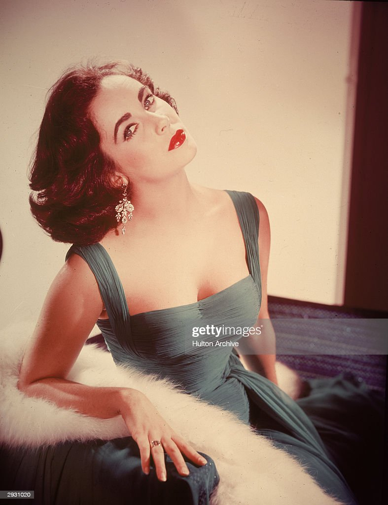 Portrait of British-born actor Elizabeth Taylor in a form-fitting green dress as she sits with her head tilted back exposing her neck, circa 1950s.